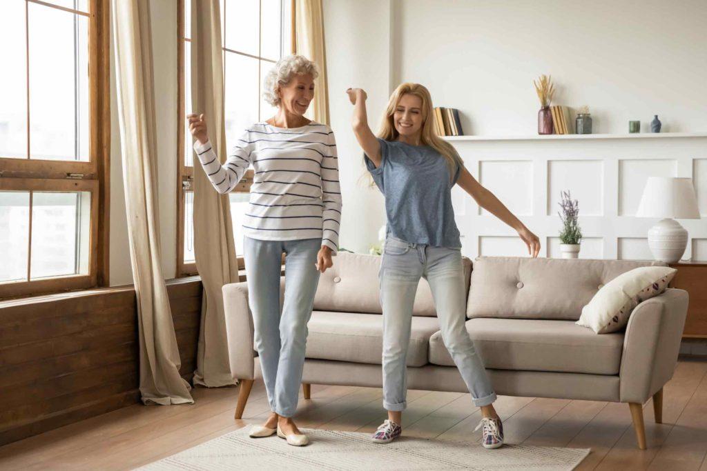 Ältere Dame tanz mit Tochter aus Freude wegen Wechsel von PKV zu GKV